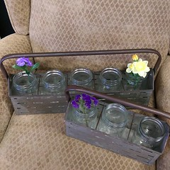 We love these jars in their metal carriers. They make great flower vases but could be used for several other things too!! #TheFunkySister #FlowerDistrict #Rustic #LiveSimply #LincolnNe #LNK (The Funky Sister) Tags: instagram the funky sister