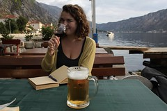 Take Note (danieljbec) Tags: ella becker kotor montenegro beer wine water sea mountains restaurant bar al dente notes notebook pen smile smiling girl woman amber sunset summer beautiful green drinking drinks outside trees seaside bench table
