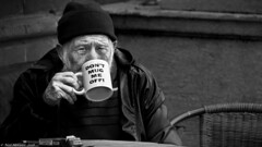 It's a mugs game. (Neil. Moralee) Tags: neilmoralee man old mature drinking mug tea coffee hat wooley wrinkles craggy black white blackandwhite bw bandw mono monochrome sitting chair logo sign cup nikon d7200 neil moralee alone lonely insular grumpy protest smoke smoker cigarette tobacco