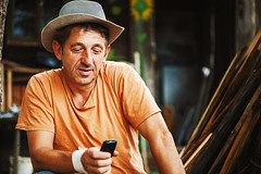 Portrait of a Country Man (dejankrsmanovic) Tags: man portrait hat cloth person rural cowboy resting communicating communicate mobile phone cell chat somebody male body active sitting outside outdoors forest wood candid natural senior older shirt orange ordinary relaxed smile face facial expression calm household lifestyle serbia balkans