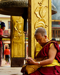 Tibetan Buddhist Nun checking her phone beside the bell at Boudhanath Stupa in Kathmandu, Nepal (BryonLippincott) Tags: nepal boudhanathstupa asia centralasia religion temple kathmandu tibetan prayerwheel cylindrical sanskrit nepalese nepali asian southernasia inside indoors day daytime travel destination tradition traditional culture heritage religious hindu hinduism spirituality interior old ancient building architecture exterior facade buddhist buddhism stupa monument nun buddhistnun tibetianbuddhistnun butterlamps