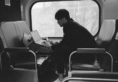 Metra Train Office. (Jovan Jimenez) Tags: canon eos rebel t2 ef 40mm stm f28 kodak tmax 3200 black white gray bw monochromatic monochrome people analog analogue 300x kiss7 metro train metra transportation travel grain laptop notebook typing working office streetphotography