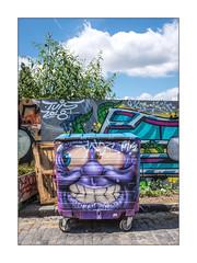 Street Art (Hull Graffiti), East London, England. (Joseph O'Malley64) Tags: hullgraffiti streetart streetartist urbanart publicart freeart graffiti eastlondon eastend london england uk britain british greatbritain art artist artistry artwork mural muralist wheeliebin rubbishbin dumpster hopper hordings fencing woodenfencingpanels plywoodpanels planter buddleia granitekerbing cobbles cobblestones cobbledroadsurface doubleyellowlines noparkingatanytime parkingrestrictions weeds character urban urbanlandscape aerosol cans spray paint fujix fujix100t accuracyprecision