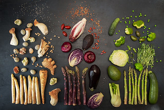 Plant based modern flat lay big set collection white red purple green vegetables on black background. Asparagus, red cabbage, avocado, eggplants, onion. Healthy food concept. Overhead. Top view.