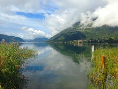 Lake Ossiach, Carinthia, Austria, in the morning (echumachenco) Tags: serene outdoor landscape september morning iphone österreich austria kärnten carinthia mountainside mountain water lake ossiachersee ossiach sky grass tree forest cloud