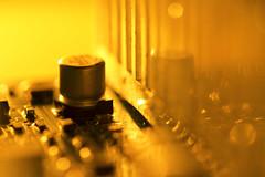 Pump up the jam (alideniese) Tags: macromondays insideelectronics 7dwf anythinggoesmondays macro closeup reflection small tiny components amplifier heatsink knob fins electricalcircuit bokeh colour alideniese bright gold yellow orange light