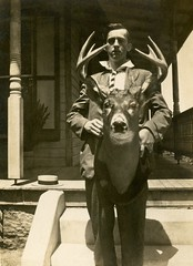 A Man and His Deer Head (Alan Mays) Tags: ephemera postcards realphotopostcards rppc photos photographs foundphotos portraits men clothes clothing suits ties neckties collars hats strawhats holding shadows animals deer dearheads antlers mounted mounts heads animalmounts houses porches strange unusual antique old vintage