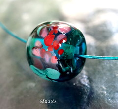 Shona (Laura Blanck Openstudio) Tags: openstudio openstudiobeads glass murano handmade art beads single focal bead fine arts artist artisan round donut nugget big holes shiny bright bold frit whimsical funky odd abstract asymmetric earthy organic made usa boutique upscale boho soho urban chic contemporary transparent translucent one kind jewelry necklace pendant stainless steel choker lampwork published winner show festival teal green bottle pine emerald blue jungle lagoon red coral pink mermaid rose mauve speckles aqua turquoise ocean marine navy night