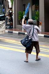 Stop that bus! (jeremyhughes) Tags: singapore street man elderly uncle singaporeuncle city bus omnibus umbrella wave waving nikon d300s nikkor 18200mmf3556 nikkor18200mmf3556gvr bodylanguage gesture gesturing road