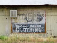 small town ghost (Black Cat Bazaar) Tags: western ranch clothing ghostsign corrugated metal building warehouse abandoned orland california ca northerncalifornia weeds dry exterior sign faded americana
