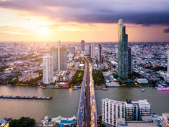 Aerial view of Bangkok skyline and skyscraper with light trails on Sathorn Road center of business in Bangkok downtown. Panorama of Taksin Bridge over Chao Phraya River Bangkok Thailand at sunset. (MongkolChuewong) Tags: aerial aerialview apartment architecture asia bangkok bank blue bridge building business capital chaophrayariver city cityscape condo condominium district downtown drone droneview grass high hotel light metropolis modern office reflection residence river roof shadow skyline skyscrapers sunrise sunset taksin thai thailand top tower town travel urban vertical view water waterfront windows krungthepmahanakhon th