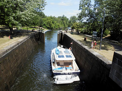 A pleasure craft from the USA heading north, waiting within the Rideau Canal's Hogs Back Locks in Ottawa, Ontario (Ullysses) Tags: pleasurecraft bateaudeplaisance hogsbacklocks rideaucanal locks11and12 écluses11et12 unescoworldheritagesite rideauwaterway nationalhistoricsiteofcanada canalrideau lieuxhistoriquesnationauxducanada patrimoinemondialdelunesco ottawa ontario canada summer été intotheblue
