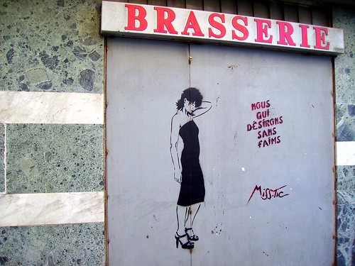 "graffiti by miss tic: a slender woman standing, one hand behind head, head a bit bowed, next to the words: ""Nous qui désirons sans faims"""