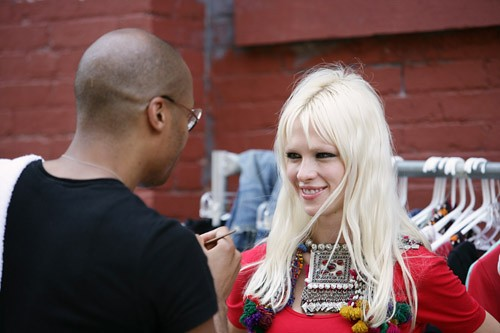 Rudy Miles, make-up artist from Aveda, does make-up for Olga Bakhmat (of Supreme Management model agency) for Fashion Fights Poverty shot on location in DUMBO, New York.
