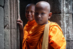 Young Monks: Bayon (mboogiedown) Tags: world travel friends boy orange heritage history boys smile face stone contrast asian amazing ancient asia cambodia cambodian serious opposite buddha buddhist south religion young expressions culture belief buddhism east holy monks siem reap sacred thom southeast tradition angkor wat enigmatic monastic saffron sangha bayon robes kampuchea cambogia 123travel reab camboge beatravelernotatourist itsallaboutthepeople reasontolearnkhmer livingfaith ifthephotographerisinterestedinthepeopleinfrontofhislensandifheiscompassionateitsalreadyalottheinstrumentisnotthecamerabutthephotographer~evearnold