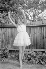 Ballet pose in the garden (vintage ladies) Tags: vintage portrait people photograph photo blackandwhite female ballet garden girl smile smiling dress bow fence eoshe