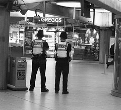 Do You Fancy A Doughnut ? (tcees) Tags: westminsterundergroundstn london sw1 londontransport jubileeline districtline circleline police greggs bakers tiles floor light newspaperstand urban x100 fujifilm finepix streetphotography street bw mono monochrome blackandwhite men metro tube sign people uk britishtransportpolice