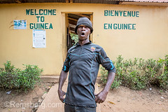 Adult African male stands in powerful stance with mouth agape in front of  Republic of Guinea border crossing. (Remsberg Photos) Tags: africa agriculture ganta liberia guinea portait adult male strong strength power confrontational energetic stable steady tough determined forceful resolute african welcome outdoors border republicofguinea
