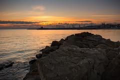 calm sea (gianlucamulone) Tags: canon 100d sea november sunset red sun rocks sky italy waves calm