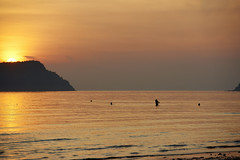 Woman swimming at sunrise Sam Roi Yot Beach, Thailand (BryonLippincott) Tags: thailand bay thai beach seaside resort rural town village tourism tourist morning early trees peaceful quiet empty deserted ocean waves sunrise goldenhour silhouette backlight woman swimming wading people