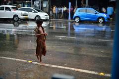 Oblivious (sanat_das) Tags: d800 50mm oblivious esplanade kolkata raining streetphotography boy