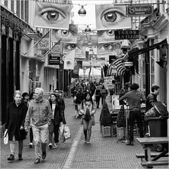 Can't take my eyes off of you (John Riper - AWAY FOR AWHILE) Tags: johnriper street photography straatfotografie square vierkant bw black white zwartwit mono monochrome netherlands candid john riper sgravenhage denhaag thehague fuji fujifilm xt2 18135 eyes people shopping banners