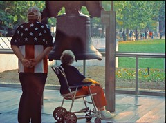 Patriotic couple at Liberty Bell (tvdflickr) Tags: film nikon f4 pennsylvania philadelphia usa libertybell tourist man woman patriots proud viewers photobythomasdriggers tvdimages photobytomdriggers thomasdriggersphotography nps
