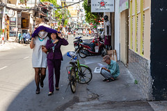 Vietnamese women hide from the sun on Bui Vien Street in Ho Chi Minh City (Evgeny Ermakov) Tags: asia asian buivien buivienstreet hochiminh hochiminhcity saigon southeast southeastasia vietnam vietnamese bicycle candid city day daylight daytime famous hide life local man motorbike newspaper old people place read senior shop street sunlight sunny tourism tourist touristic traditional travel typical woman women editorialuse