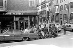 041071 19 (ndpa / s. lundeen, archivist) Tags: nick dewolf nickdewolf blackwhite monochrome blackandwhite 35mm film photographbynickdewolf bw may 1971 1970s boston massachusetts beaconhill people youngpeople streetlife streetphotography candid charlesstreet car vehicle automobile parkedcar corner intersection lamppost stoplight street chestnutstreet 31charlesstreet awning flowerstore guildsflowers seated sitting onthecurb inthestreet cars vehicles automobiles crosswalk pedestrians building buildings store shop florist storefront denim flannel citylife man men youngman youngmen woman women youngwoman youngwomen clothes clothing longhair