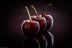 Three cherries...and a devillish reflection? (The Frustrated Photog (Anthony) ADPphotography) Tags: category england foodanddrink places cherry fruit three reflections narrowdepthoffield depthoffield dof closefocus closeup monochrome lowkey reflectedlight mirror canon70d canon sigma105mmmacro breakingrules dark food edible