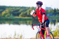 Male Cyclist Having a Rest. Drinking Refreshing Liquid from the Bottle. Shot Made Outdoors. Horizontal Image (DmitryMorgan) Tags: 3039years 30s activity adult athlete bicyclist bike biker boy caucasian competition concentration control cycle cycling cyclist effort endurance equipment fitness helmet individualsports male man motion onthemove one outdoors outfit panningtechnique portrait professional pursuit race ride riding speed sport sportsclothing summer training velocity vitality white young