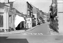 High Street, Seaford, Sussex, 1958 (Lady Wulfrun) Tags: highstreet southstreet seaford sussex august 1958 1950s seaside resort town macfisheries ellismartin ecjeffery shop shops haltsign roadsign prewarboys chemist robins wine merchant sayers sayer clockbakery dixeys opticians