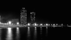 A quiet night (Fnikos) Tags: sea water bay seascape landscape waterfront beach shore seashore sand coast sky city building tower architecture light people dark darkness blackandwhite monochrome outdoor