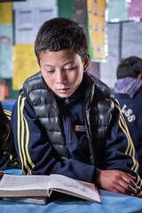 Schoolboy reading in school class in Laya - Gasa District - Snowman Trek - Bhutan (PascalBo) Tags: nikon d500 asie asia southasia asiedusud drukyul drukgyalkhap bhutan bhoutan འབྲུག་ཡུལ། འབྲུག་རྒྱལ་ཁབ་ snowman trek trekking hike hiking lunana gasa himalaya himalayas jigmedorjinationalpark laya layap people kid child enfant boy garçon school pascalboegli indoor indoors indigenous