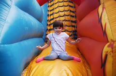 Small Girl on Trampoline (dejankrsmanovic) Tags: girl child kid trampoline fun entertaining amusement color colorful game concept people person somebody one conceptual facial expression active hand tube path channel corridor pose cute smile shirt outdoor
