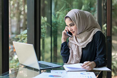 Pretty woman wearing hijab in front of laptop search and doing office work, business, finance and workstation concept. - Credit to https://www.lyncconf.com/ (nodstrum) Tags: work home time today hardwork working workethic homework officework cubicle workplace money jobs networking desk