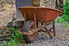 Wheelbarrow carrying history (FotoFloridian) Tags: wheelbarrow wheel barrow outdoors cart equipment gardening transportation tire old gardeningequipment machinery sony alpha a6000