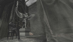 Sitting With The Angel Warrior (Loegan Magic) Tags: secondlife versus statue angel warrior chair sitting male model pose dark curtain