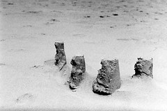 Castles Made of Sand (bac1967) Tags: leicaiiif leicarangefinder leica leitz summitar5cmf2 summitar summitarlens panatomicx kodak kodakpanatomicx kodakfilm beerenol beerol beer pabstblueribbonbeer pabst oregon or blackandwhite blackandwhitefilm blackwhite bw monotone monochrome black white pacificnorthwest pnw 135film 35mmfilm sandcastle beach sand sea ocean pacific pacificocean florenceor florence southjetty jetty