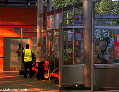 Modern Communication 18 (M C Smith) Tags: busstation station busshelters phone people women men bus buses red orange glass posters advertising numbers letters pentax istd grey seats chrome bag cupboard symbols trees green sky blue lamp shadows