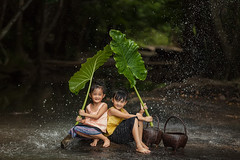 Children are happy to play and hold green umbrellas from nature in rainy autumn day. (Visoot20) Tags: asian kid rural poor water thailand river vietnam boy happy playing lifestyle child people fresh summer fun kids outdoor myanmar cambodia caucasian indonesia joy nature rain happiness sunset rainy funny splash expression laos play person cute face space sun vacation standing recreation rustic season green active children enthusiasm wet laugh