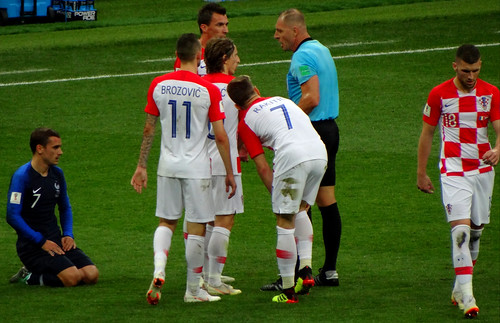 Croatia players surround the referee as Antoine Griezmann kneels on the ground after being fouled in the 2018 World Cup Final