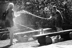 I'll wet you ... (Klaus Wessel) Tags: olympus omd em10 1240mm mft blackwhite bw monochrome wasser nass spritzen menschen street streetlife