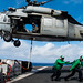 Sailors prepares to take cargo from the flight deck of.