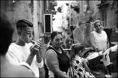 (Spanish Quarters Clichè) (Robbie McIntosh) Tags: leicam9p leica m9p rangefinder streetphotography 35mm leicam summilux leicasummilux35mmf14i summilux35mmf14i autaut summilux35mmf14preasph man strangers napoli spanishquarters processionemadonnadelcarmine procession religion cigarette eyecontact woman