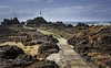 Corbiere Lighthouse, Jersey. (Peter R. Howard) Tags: corbiere lighthouse jersey rocks sea seaweed sand waves foam sky cloulds causeway path pools peterrhoward photography
