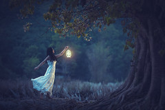 Beautiful girl in white holding a lantern in the autumn forest shining under the trees. (Pramote Polyamate) Tags: lantern forest holding woman girl beautiful white background light fashion night young dark magic autumn magical wood dress beauty lamp halloween female portrait park fantasy hands fire mystery candle mysterious tale fairytale nature blue costume wreath witch people art black adult under trees