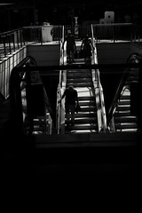 Shopping centre symmetry ( nearly ). (ianmiller6771) Tags: blackandwhite bw whiteblack streetphotographyuk streetphotography candid shoppingcentre symmetry fuji stairway giraffe mirrors reflections 35mm handrail shinymetal shadow deepshadow