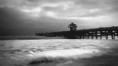 Pacific Edge (emiliopasqualephotography) Tags: blackandwhite beach shore ocean waves clouds pier water