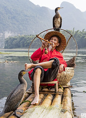 KIng of the Raft (lc99photography) Tags: cormorantfisherman fisherman cormorantfishing cormorant birds wildlife raft bambooraft river lijiang liriver guilin guangxi travel red oldman smoke pipesmoking hat landscape mountains karst karstformation